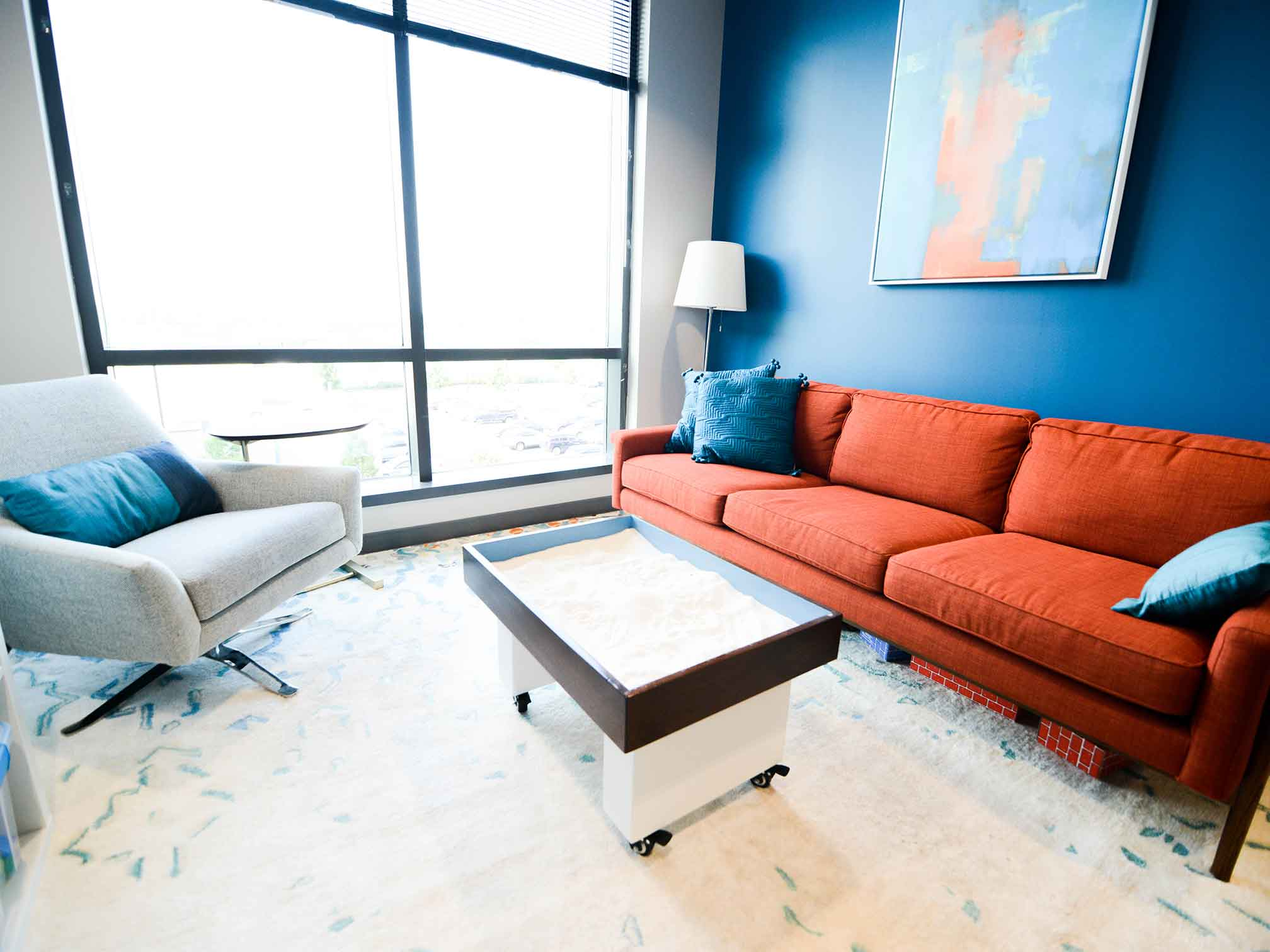 Beautiful therapy room with couch, chair and sandbox for child counseling and therapy. Your child can get help in play therapy in Ohio and Indiana for child counseling with ThrivePointe child therapists