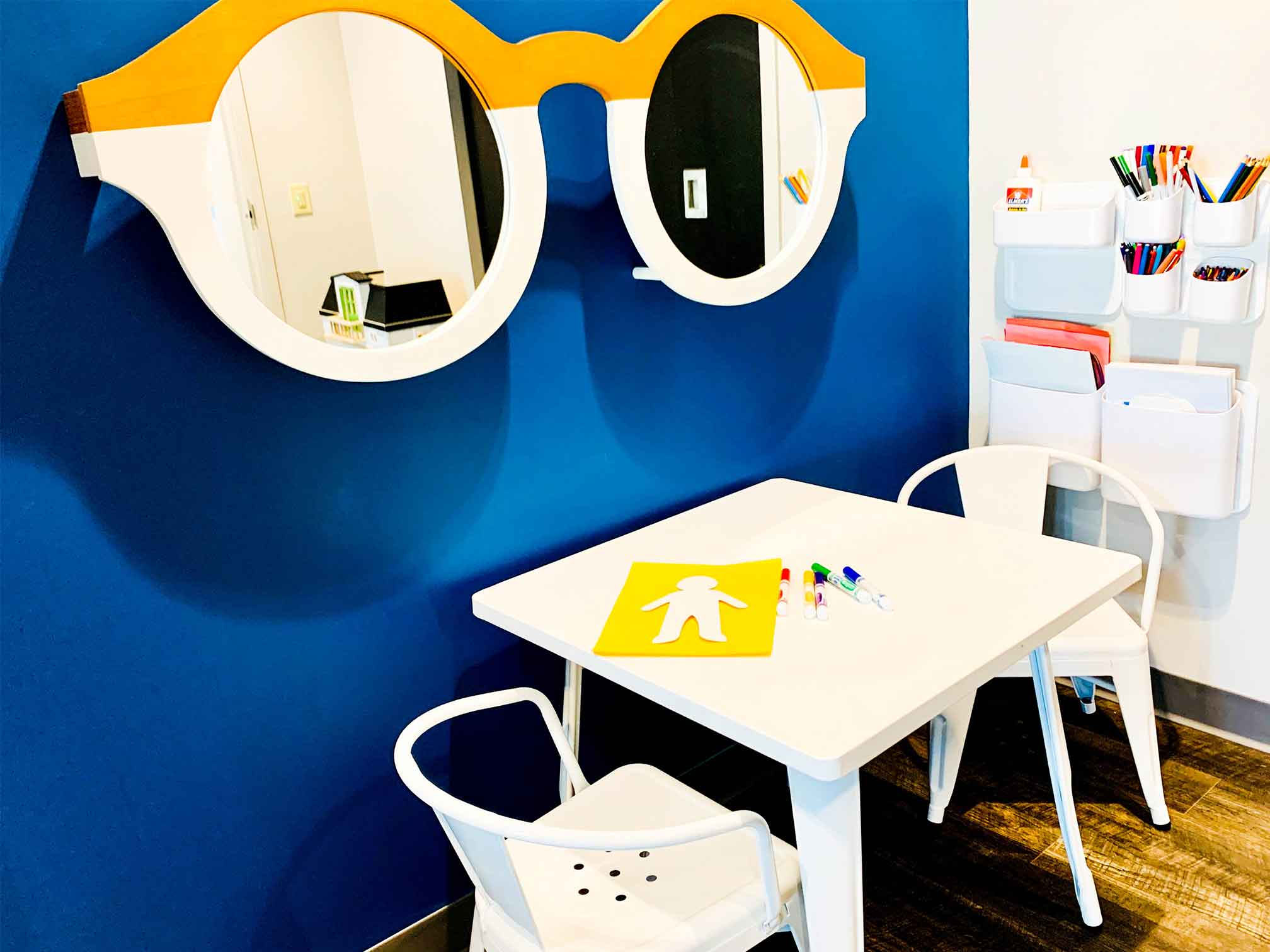 Room with a table and chairs with a big pair of mirrored glasses and craft supplies, decorated in bright colors for child counseling and therapy. Your child can get help in play therapy in Ohio and Indiana for child counseling with ThrivePointe child therapists