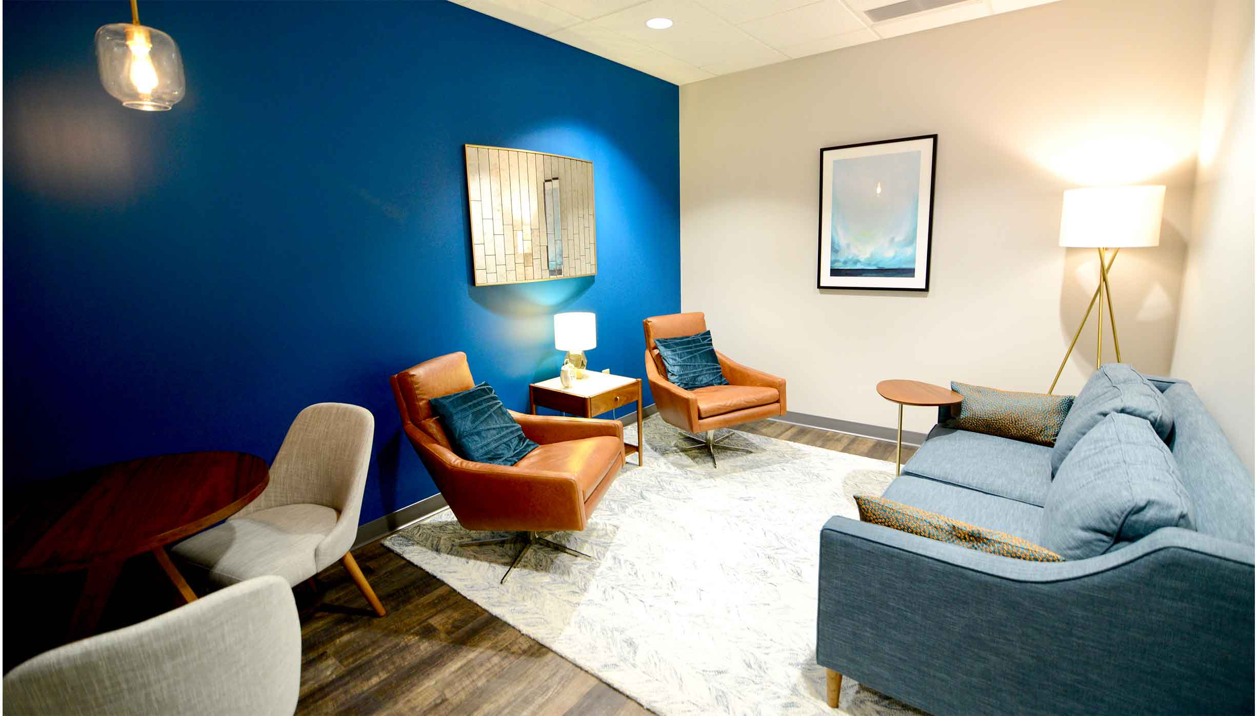 Family therapy room with a welcoming blue wall, a couch, chairs and tables, and modern art for a relaxed family counseling experience in Liberty Center. ThrivePointe Counseling helps adults and children through family therapy in Liberty Township, OH 45069